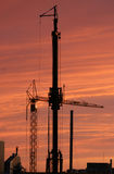 Construction cranes. In Tallinn  silhouetted against a fiery sunset Royalty Free Stock Photo