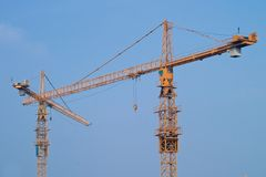 Construction cranes. Two crossed yellow cranes over blue sky on a construction site Royalty Free Stock Photography