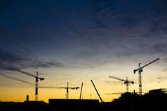 Construction cranes. Construction site and crane silhouettes under night blue and yellow night sky Royalty Free Stock Image