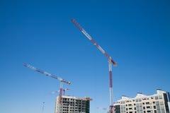 Construction cranes above buildings Stock Photo