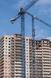 Construction cranes against a background of high-rise building. Two construction cranes against a background of high-rise building under construction Stock Images
