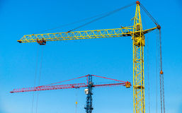 Construction cranes on a background of blue sky Royalty Free Stock Image