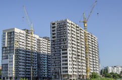 Construction cranes on the background of buildings under constru Stock Image