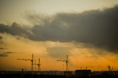 Construction cranes on the background of the sunset. royalty free stock photography