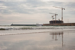 Construction cranes on beach. A construction site with cranes on a beach Royalty Free Stock Images