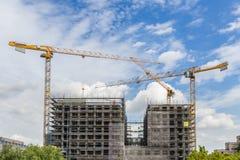 Construction cranes at big building construction site Stock Photos