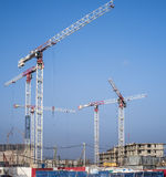 Construction cranes on a blue sky background. Construction cranes begin to build a new residential complex on a blue sky background with industrial smog stock images