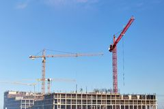Construction cranes , construction on blue sky background. stock image