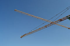 Construction cranes. The boom of construction cranes at construction site Royalty Free Stock Image
