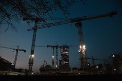 Construction cranes build houses in a big city.night. warsaw spire. Warszawa. City. Poland. Street. business center Stock Images