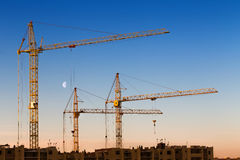 Construction cranes, building against blue sky with Moon at dawn Royalty Free Stock Images
