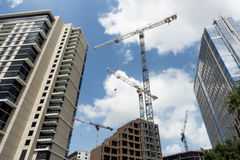 Construction cranes building new buildings in a downtown area Royalty Free Stock Photos