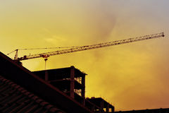 Construction cranes and Buildings Backlit on evening sky Stock Images