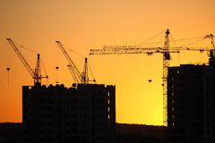 Construction cranes with built houses on the background of the s Royalty Free Stock Photos