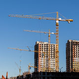 Construction cranes and built houses on blue sky background Stock Photo