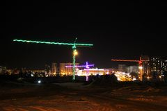 Construction cranes at a construction site, colored light at night, lights and LEDs. Outdoors royalty free stock photography