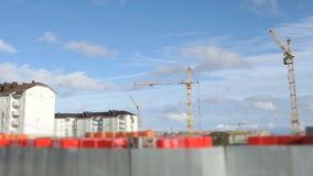 Construction cranes at construction site. Construction cranes working on high-rise building stock footage
