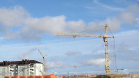 Construction cranes at construction site. Construction cranes working on high-rise building stock video footage