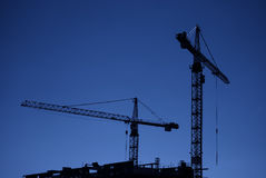 Construction cranes at dusk Royalty Free Stock Photos