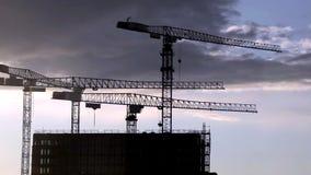 Construction cranes at dusk stock video