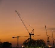 Construction cranes in evening Stock Photos
