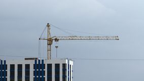 Construction cranes and high-rise building under construction against blue sky. stock photos