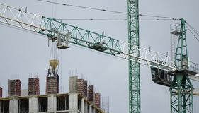 Construction cranes and high-rise building under construction against blue sky. royalty free stock photography