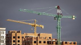 Construction cranes and high-rise building under construction against blue sky stock photos