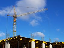 Construction cranes and high-rise building under construction against blue sky. Royalty Free Stock Photos