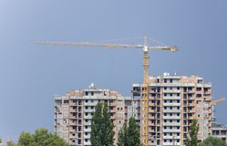 Construction cranes and high-rise building under construction against blue sky. Stock Images