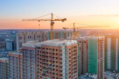 Construction cranes of high-rise residential buildings in the big city, view of the evening sky royalty free stock photos