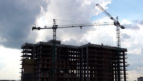 Construction cranes industrial timelapse. This stock footage presents the time lapse of a construction site. It shows two huge cranes lifting construction stock video footage