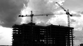 Construction cranes industrial timelapse video. This stock black and white footage presents the time lapse of a construction site. It shows two huge cranes stock video
