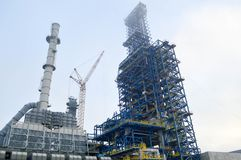 Construction with cranes of a large blue chemical plant at an oil refinery. Petrochemical plant Stock Photos