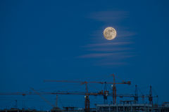Construction cranes in the light of the full moon Royalty Free Stock Images