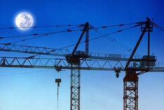 Construction cranes and moon Royalty Free Stock Image