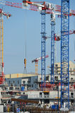 Construction cranes and site against a blue sky Stock Photography