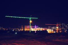 Construction cranes at a construction site, colored light at night, lights and LEDs. Outdoors stock images