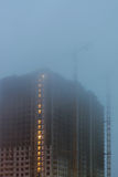 Construction cranes on the site, unfinished houses, fog covers the upper floors, evening twilight, the lighting of the Royalty Free Stock Image