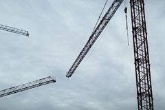 Construction cranes on the sky background. Construction site. Black construction cranes on the background of grey clouds Royalty Free Stock Photo