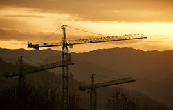 Construction cranes. Three construction cranes in front of mountains during sunset Royalty Free Stock Photography