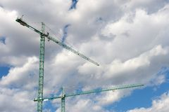 Construction cranes. Two big construction cranes with a background of blue sky with white clouds Stock Image