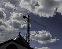 Construction cranes. Two construction cranes on cloudy sky background Royalty Free Stock Images