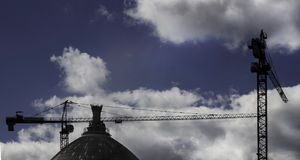 Construction cranes. Two construction cranes on cloudy sky background Stock Photos