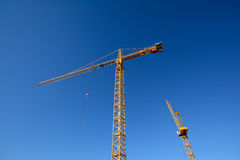 Construction cranes. Two yellow construction cranes at a new building site Royalty Free Stock Photo