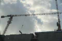 Construction cranes are under shade of light. With blue sky stock images