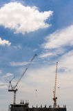 Construction cranes on unfinished hotel Stock Photography
