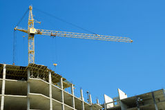Construction cranes and unfinished house Royalty Free Stock Photo