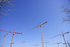 Construction cranes view over blue sky Stock Photos