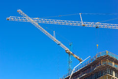 Construction cranes work in synchrony at building site. Royalty Free Stock Images
